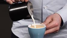 Pouring milk to make espresso drinks
